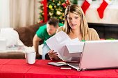 Woman goes through stack of bills during Christmas