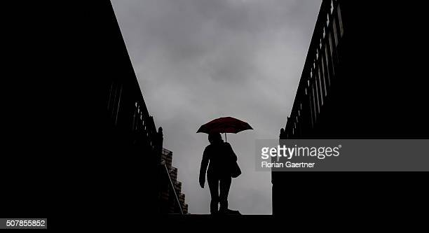 A woman goes upstairs from the metro station during rain on February 01 2016 in Berlin