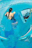 young woman going down a water slide. water Park