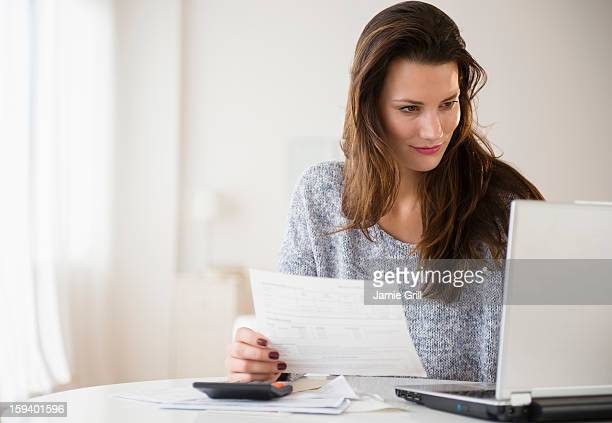 Woman going over bills with laptop computer