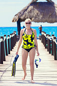 A beautiful middle-aged woman on a beach dock at a tropical resort holding her snorkel gear and ready for some fun in the ocean