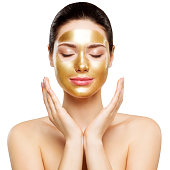 Woman Gold Mask, Beautiful Model with Golden Skin Cosmetic, Beauty Skincare and Treatment, Shot over white studio background