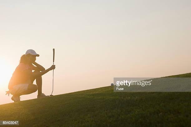 Woman Golfer Lining Up Put