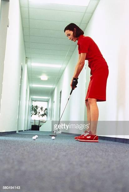 Woman Golfing in Hallway