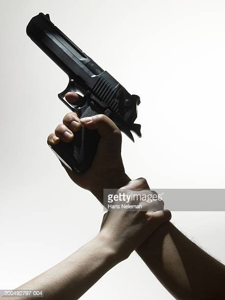 Woman grabbing man with hand gun by his wrist, close-up, side view