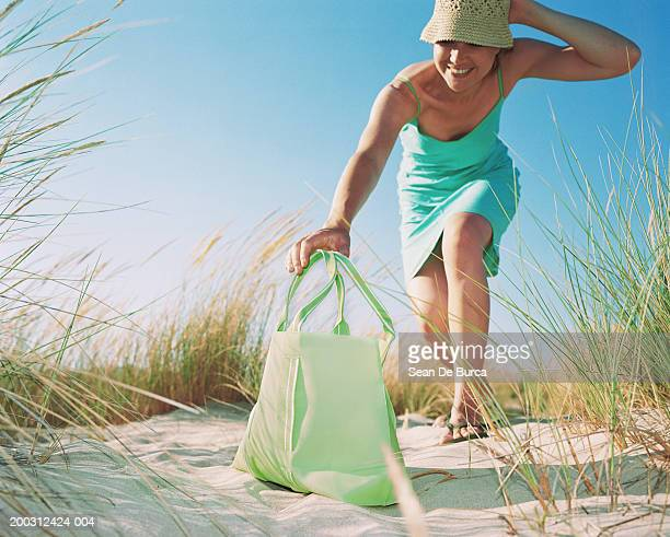 Woman grabbing tote on beach, smiling