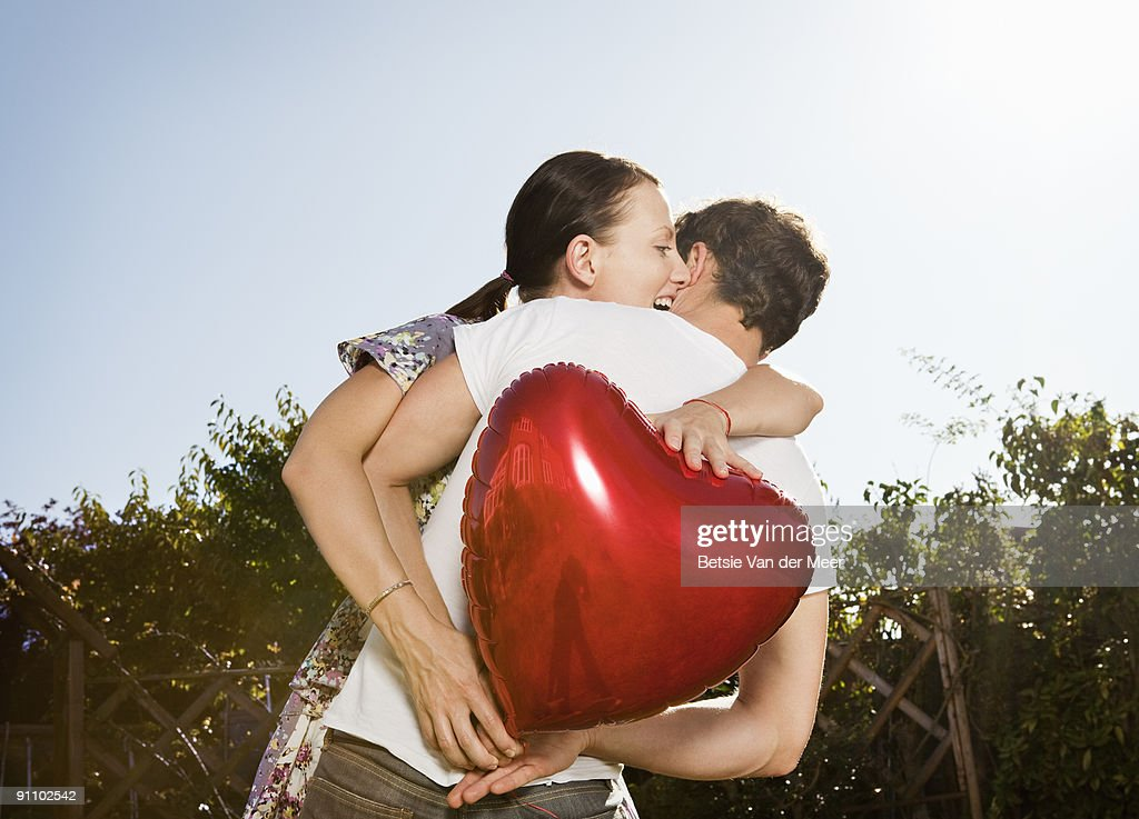 woman grabs heart shaped balloon from man. : Stock Photo