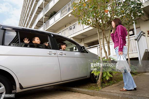 Woman greeting family in car