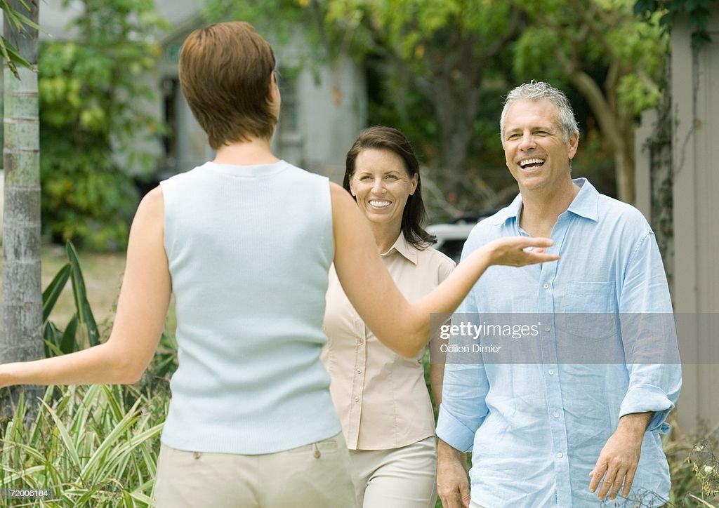 Woman greeting mature couple
