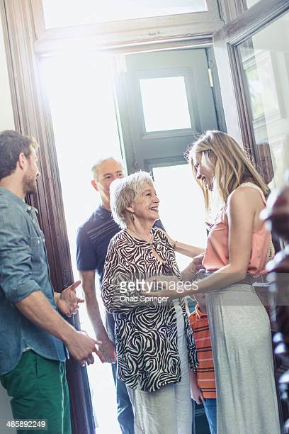 Woman greeting parents in hallway