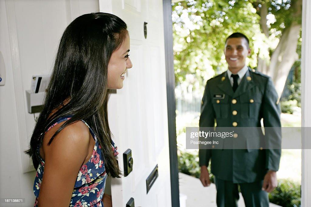 Woman greeting soldier boyfriend at door