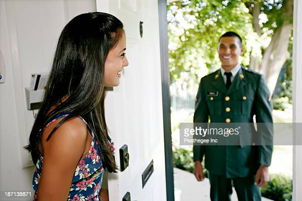 Woman greeting soldier boyfriend at door
