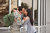 Woman greeting soldier husband returning home