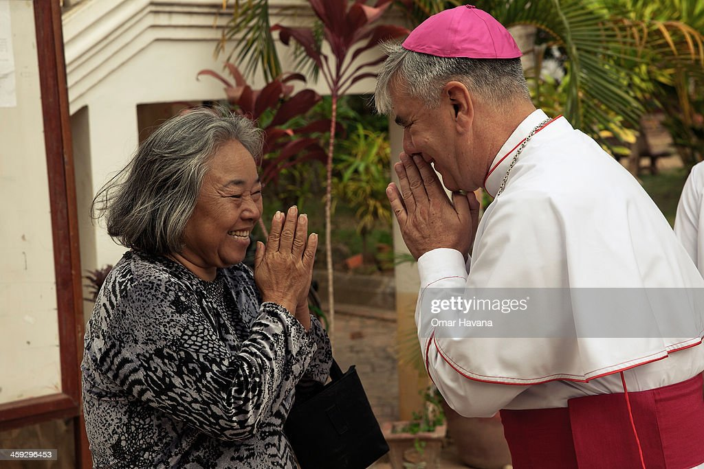 A woman greets Monsignor Enrique Figaredo moments ahead of the start of the Christmas day mass at the church of Our Lady of the Assumption on December 25, 2013 in Battambang, Cambodia. The parish at Battambang dates back to 1790 when the Catholic community first arrived. Now they serve around 1000 Catholics and 600 families.