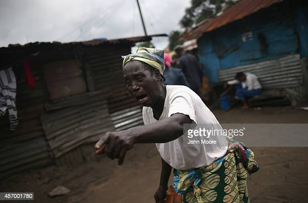 A woman grieves after Ebola burial team members arrived to take away the body of Mekie Nagbe for cremation on October 10 2014 in Monrovia Liberia...