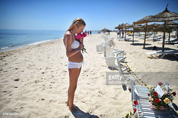 A woman grieves as she lay flowers at the beach next to the Imperial Marhaba Hotel where 38 people were killed yesterday in a terrorist attack on...