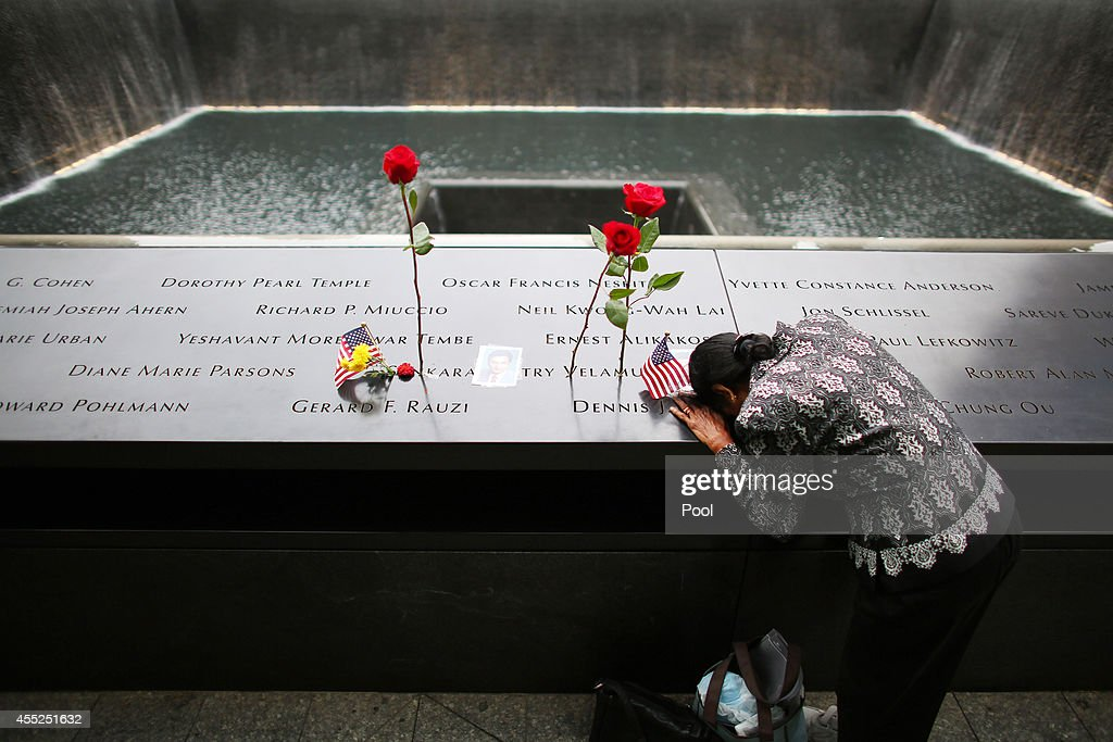 A woman grieves at her husband's memorial at South Tower Reflecting Pool before the memorial observances held at the site of the World Trade Center...