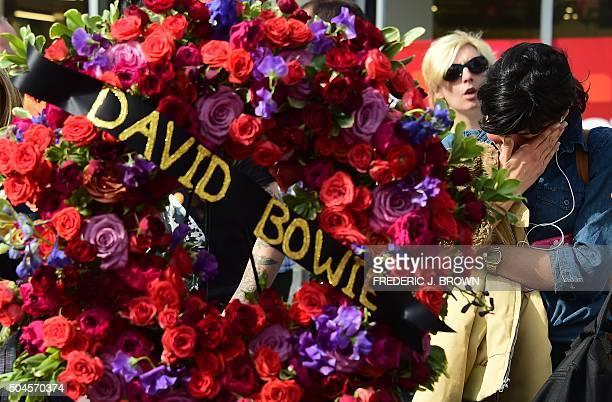 A woman grieves beside a wreath donated from the Hollywood Chamber of Commerce which was delivered to the Hollywood Star of the late British musician...