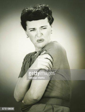 Woman grimacing, arms folded, (B&W), portrait