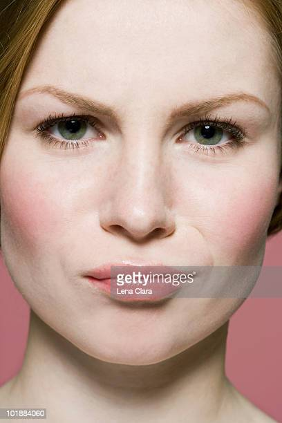 A woman grimacing in irritation, extreme close up