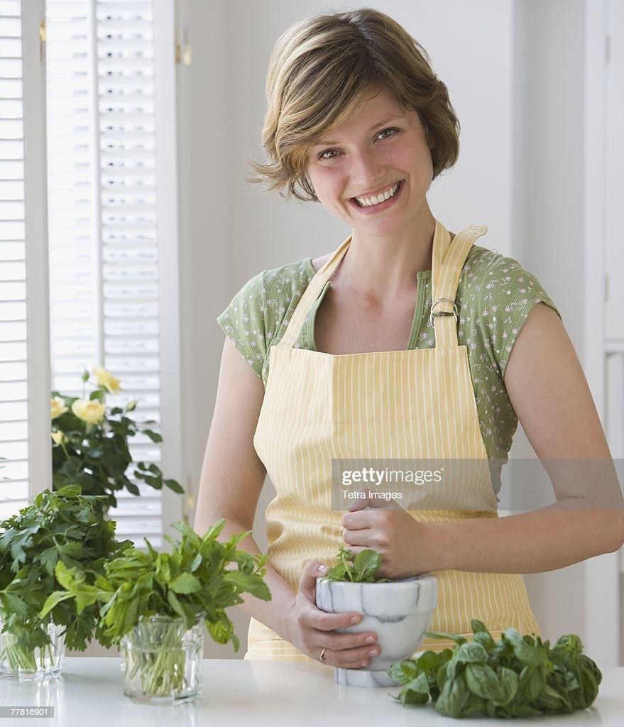 Woman grinding fresh herbs