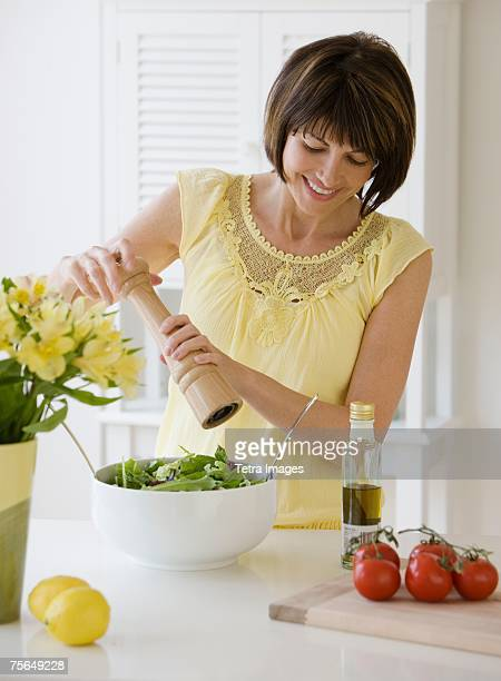 Woman grinding pepper onto salad