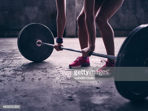 Woman gripping a barbell with heavy weights about to lift