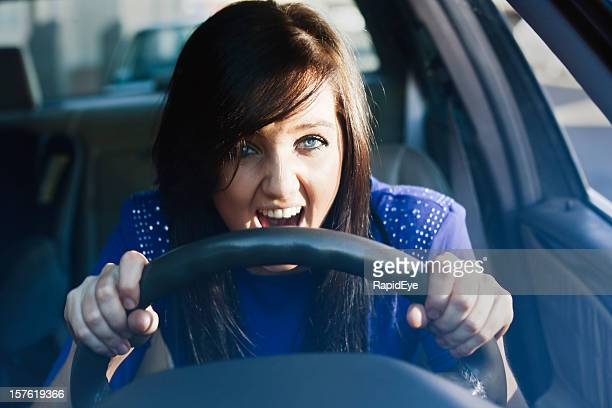 Woman grips steering wheel and yells in fear or frustration
