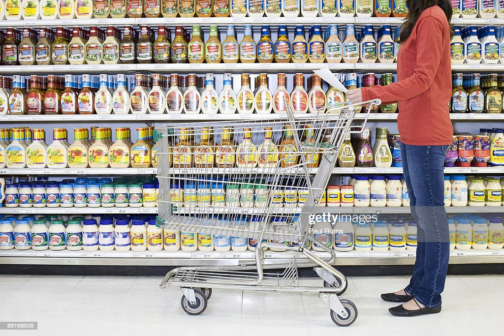Woman Grocery Shopping Looking at Grocery List  : Stock Photo