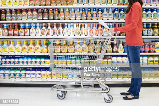 Woman Grocery Shopping Looking at Grocery List  : Bildbanksbilder