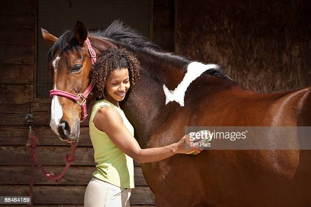 Woman grooming a horse.
