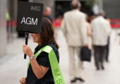 A woman guides shareholders into the Royal Festival Hall in central London on July 14 ahead of Marks and Spencer's annual general meeting AFP...