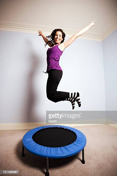 A woman gymnast in mid air above a small trampoline