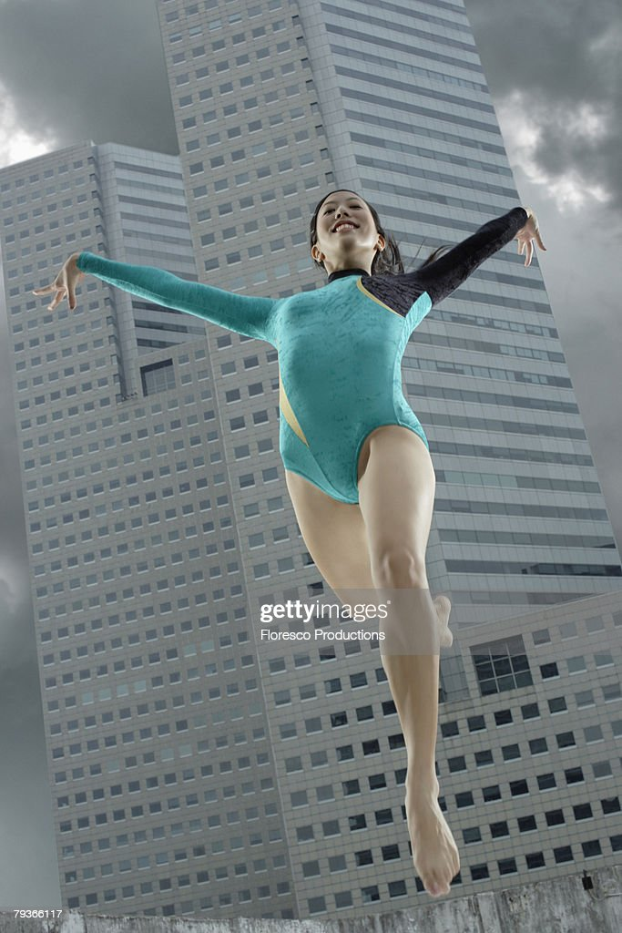 Woman gymnast outdoors jumping : Stock Photo