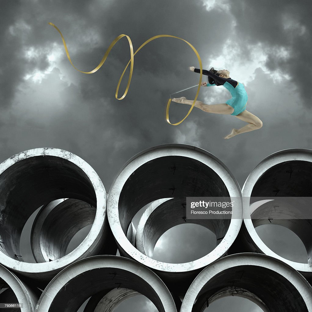 Woman gymnast outdoors on large cement cylinders jumping with ribbon : Stock Photo