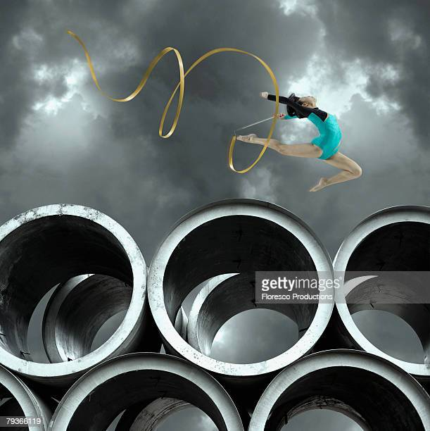 Woman gymnast outdoors on large cement cylinders jumping with ribbon
