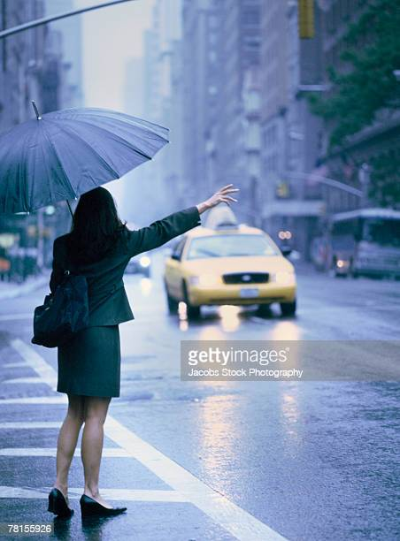 Woman hailing a taxi cab during a downpour