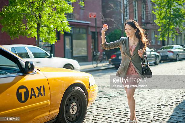 Woman hailing and running for taxicab