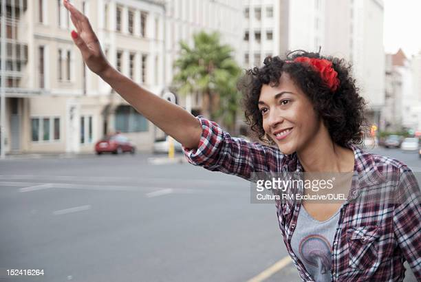 Woman hailing taxi on city street