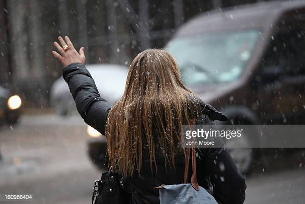 A woman hails a taxi as a major winter storm moves in on February 8 2013 in New York City Snow and freezing rain fell over Midtown Manhattan as the...