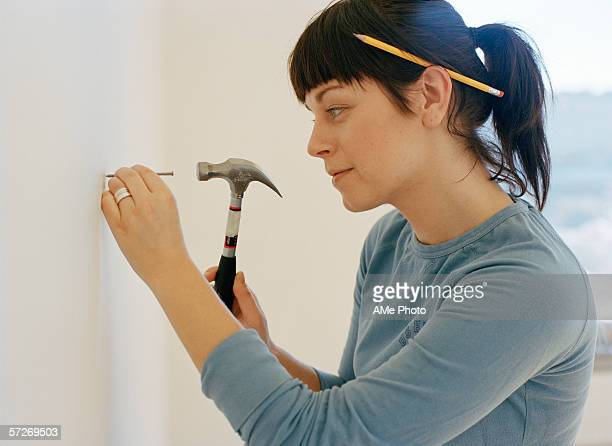 A woman hammering a nail into a wall.