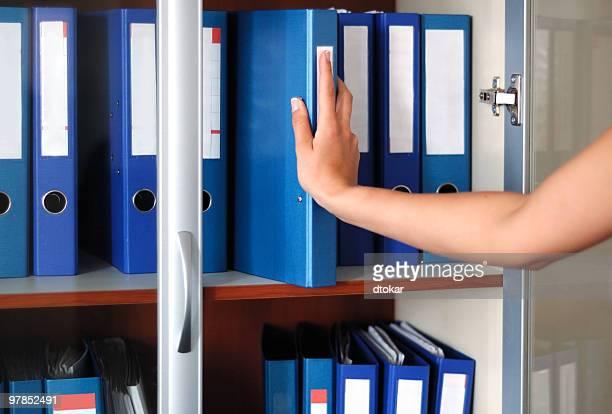 Woman hand and folders in bookshelf