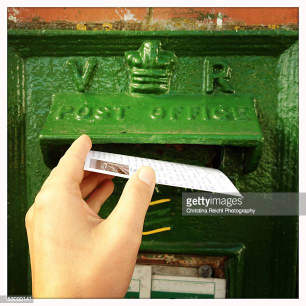 Woman hand delivering postcard in mailbox