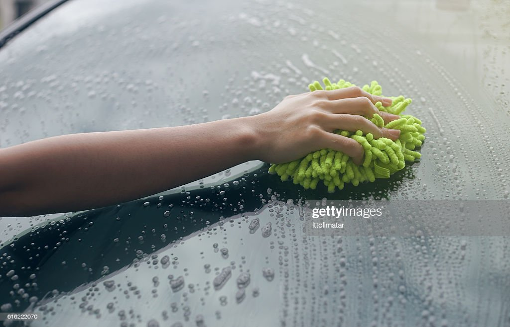 woman hand hold a brush washing over Windshield : Stock Photo
