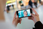 Close up of a woman hand holding a smartphone during a skype video