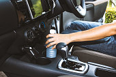 Shot of a young woman holding drinking water bottle on cup holders in car background