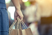 Woman hand holding shopping bags on the street in the shopping mall in vintage color tone