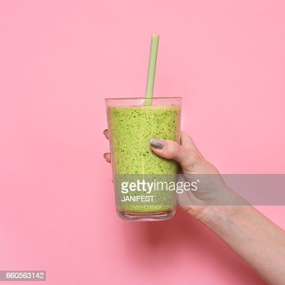 Woman hand holding smoothie shake against pink wall : Foto de stock