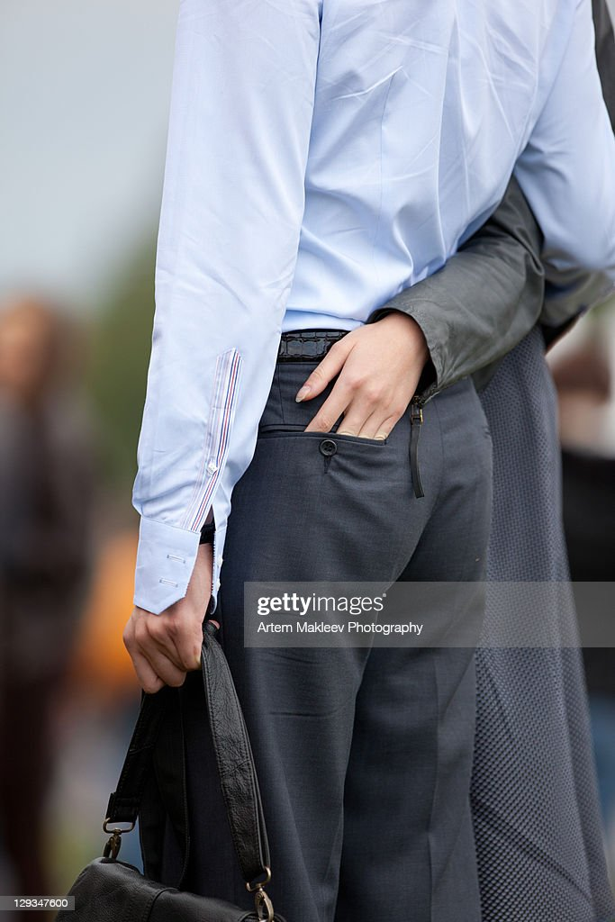 Woman hand in her boyfriend trousers hip-pocket. : Stock Photo