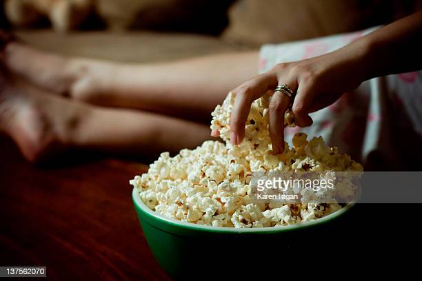 Woman hand into bowl of popcorn